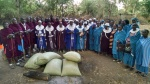 Women's and men's groups receiving gifts of ground maize from Maasai Education Foundation representatives
